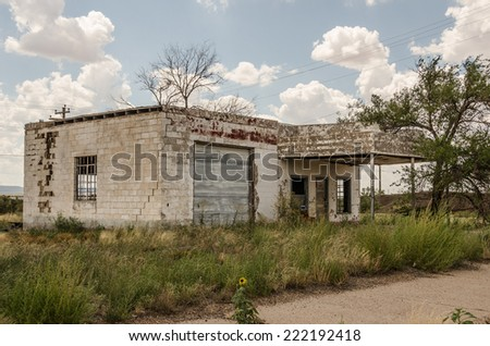 Neglected and abandoned former gas station and repair shop with a large crack in the building and lots of weeds in the yard on Route 66