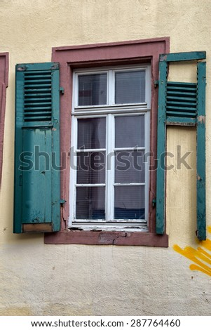 Neglected Building in Need of Repairs, Architectural Detail of Window with Broken Green Shutters and Yellow Graffiti on Wall - stock photo