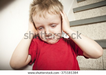 Neglected lonely child leaning at the wall - stock photo