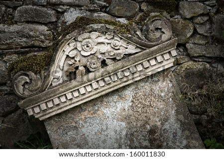 Neglected old gravestone against old stone wall. Intentional vignette with space for your text. - stock photo