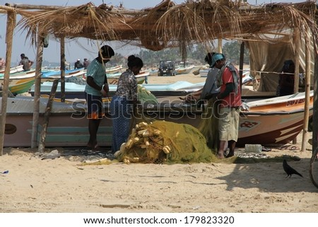 NEGOMBO, SRI LANKA - FEBRUARY 12: Fishermen sorting fish and mending nets on the beach in Negombo, Sri Lanka on the 12th February, 2014. - stock photo