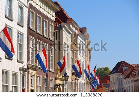 neighborhood in a dutch village with the dutch flag on queensday - stock photo