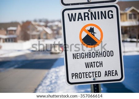 Neighborhood watch sign in a snowy Midwest suburb.
