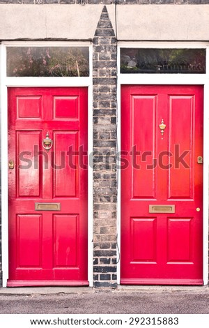 Neighbouring red wooden front doors in neighbouring homes in the UK
