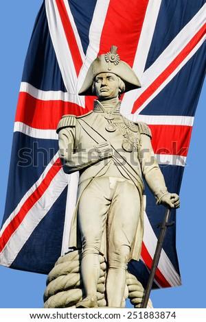 Nelson statue over Union Jack in Trafalgar Square - stock photo