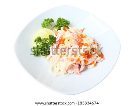 Nemo salad with squid, pepper, lollo Rosso salad, Japanese omelet and mayonnaise on white dish isolated on a white background. There is red caviar on it. Side view. - stock photo