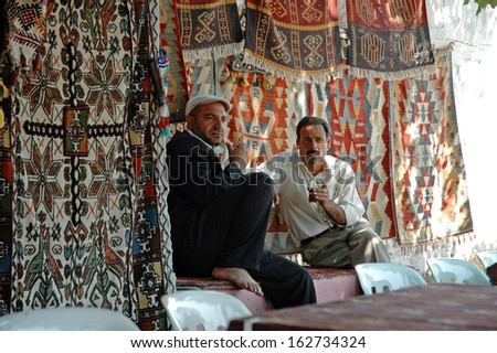 NEMRUT, TURKEY - JULY 23: Turkish carpet vendors selling their precious carpets, in a traditional turkish bazaar at a fair day, on July 23, 2006 in Nemrut, Turkey - stock photo