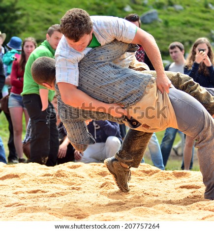 NENDAZ, SWITZERLAND - JULY 27:  A throw during a bout of swiss wrestling at the  finals of the 13th International Festival of Alpine horns :  July 27, 2014 in Nendaz Switzerland - stock photo