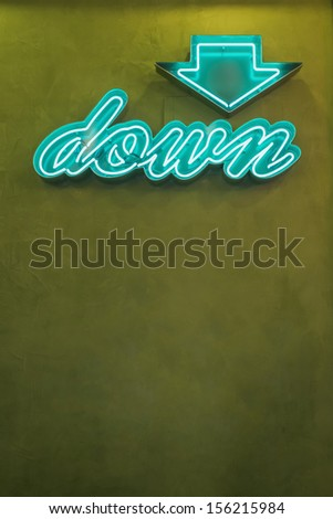 Neon down arrow sign, Seattle, Washington. Stock photo of a neon down arrow sign on a green wall with copy space. - stock photo
