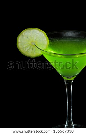 neon green martini served on a black background garnished with a lime on the rim