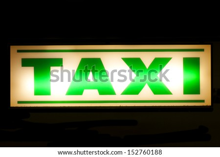 Neon green taxi sign at night - stock photo