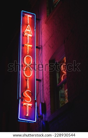 Neon lit sign tattooist on the wall of building in Soho, London - stock photo