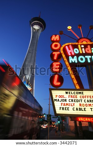 Neon motel sign and Stratosphere hotel and casino tower at dusk in Las Vegas, Nevada, USA - stock photo
