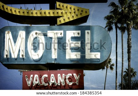 neon motel sign with palm trees - stock photo