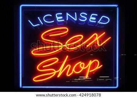 Neon sign advertising an adult licensed sex shop in a red light district