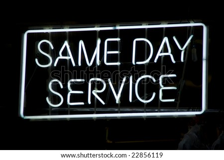Neon sign advertising same day service in the window of a Harlem, New York City dry cleaning store - stock photo