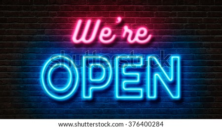 Neon sign on a brick wall - We are open - stock photo