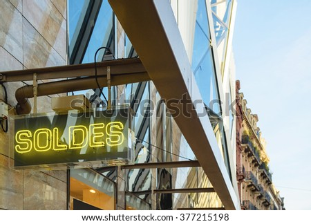 Neon sign with word SOLDES transalted as SALES from french on the corner of retail store building facade - stock photo