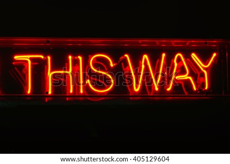 Neon THIS WAY sign; genuine traditional neon sign reading This Way; isolated on black ground  - stock photo