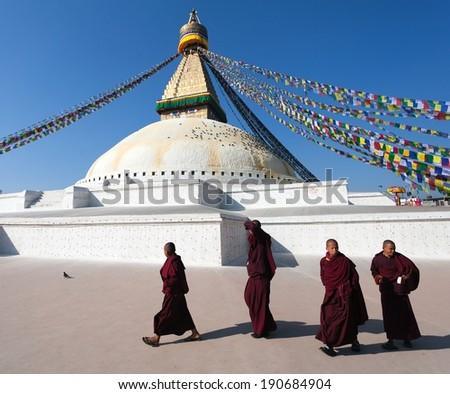 Nepal, Kathmandu -17th of December 2013: Tibetan Buddhist monks walking around Boudhanath stupa during festival  - stock photo
