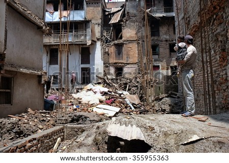 nepali man carrying child watch collapsed brick apartment in kathmandu hit by earthquake on 25 april