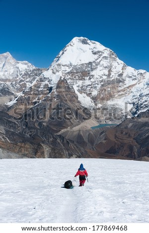 Nepali porter with Chamlang Peak (7,319 m) in background, Everest region of Nepal. - stock photo