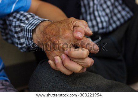 nephew holding strong grandfather's hand