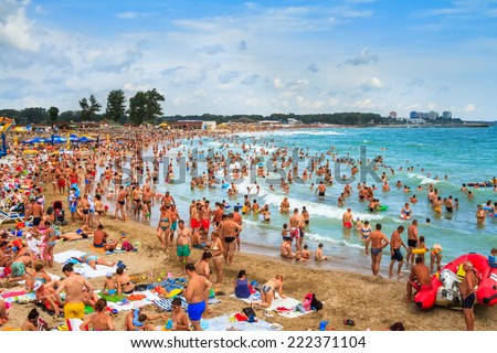 NEPTUN JUPITER, ROMANIA - AUGUST 02, 2014 Unidentified people enjoying the waves next to a crowded beach at Neptun, watched by lifeguards  - Jupiter sea summer resort - stock photo