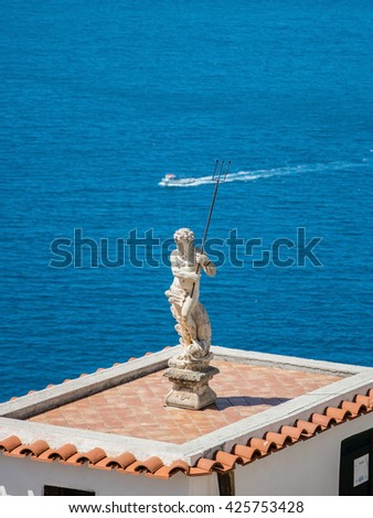 Neptune statue on top of seaside villa with cruise ship crossing - stock photo
