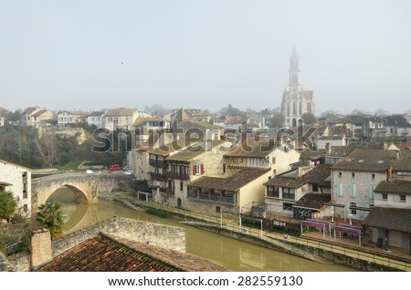 Nerac is the ancient French town lying on both sides of the Baise River. There are medieval townhouses and the cathedral in the winter mist. - stock photo