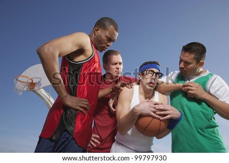 Nerd being harassed on basketball court - stock photo