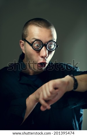 Nerd guy in glasses looking at watches and surprising - stock photo