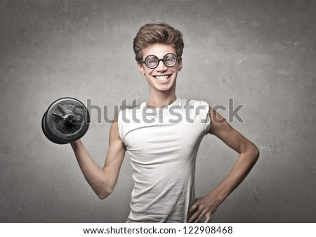 Nerd guy raising a dumbbell - stock photo