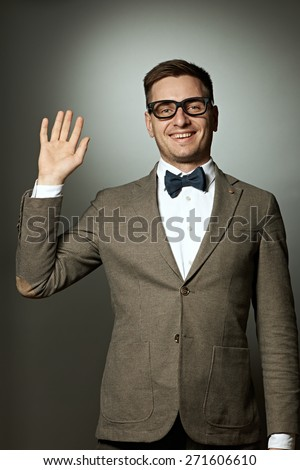 Nerd in eyeglasses and bow tie says Hello against grey background - stock photo