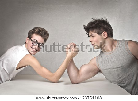 Nerd is wrestling with a muscular guy - stock photo