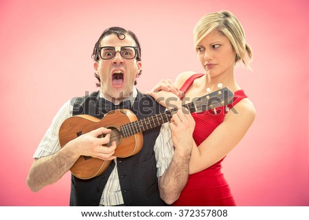 Nerd man boyfriend play ukulele love song for his girlfriend for valentine day - stock photo