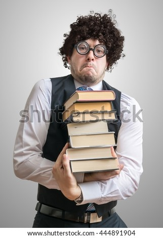 Nerd man holds many books in hands. - stock photo