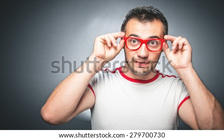 Nerd man with eyeglasses looking. Crazy guy playing with eyewear over dark gray background. Studio shot