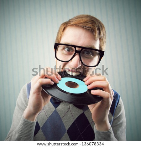 Nerd student angry, biting a vinyl record - stock photo