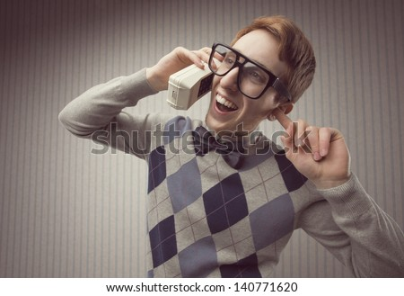 Nerd student with an old mobile phone  - stock photo