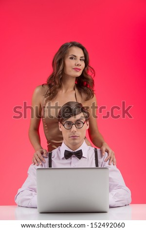Nerd with girlfriend. Confident nerd man working at the computer while beautiful young woman standing behind his back and smiling - stock photo