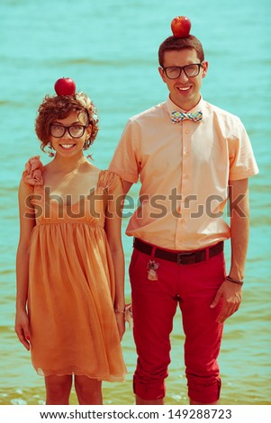 Nerds' honeymoon concept. Portrait of couple of young happy married hipsters in trendy clothes standing together on the beach with apples in their heads. Sunny summer day. Outdoor shot