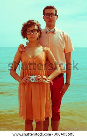 Nerds' honeymoon concept. Portrait of couple of young happy married hipsters in trendy vintage clothes standing together on the beach and making selfie. Sunny summer day. Outdoor shot