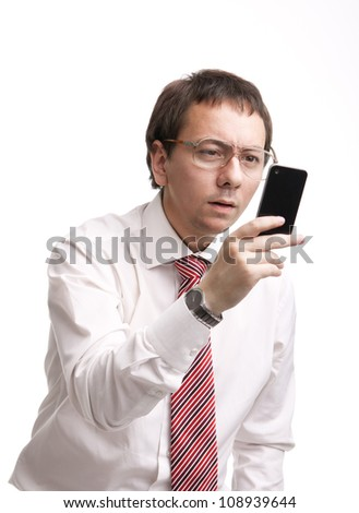 Nerdy businessman holding a smartphone and trying to read a message - stock photo