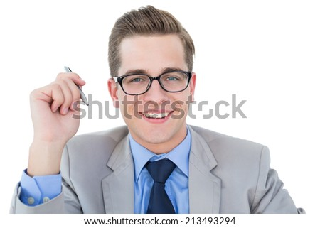 Nerdy businessman holding pen smiling at camera on white background