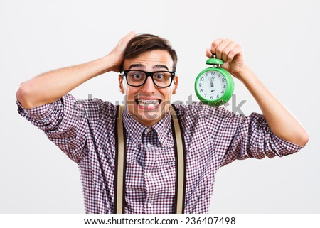 Nerdy man is in panic because he doesn't have too much time to do something.Time - stock photo