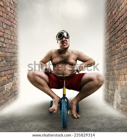 Nerdy man riding a small bicycle - stock photo