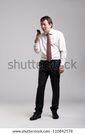 Nerdy manager holding his smartphone - stock photo