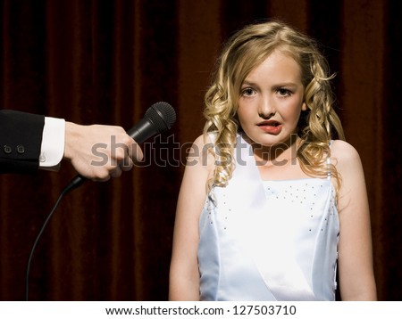 Nervous beauty pageant contestant with microphone - stock photo