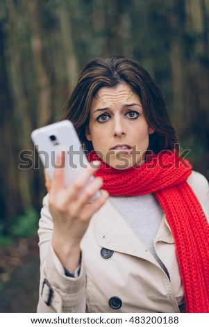 Nervous upset woman holding cellphone outdoor. Brunette girl having problems with smartphone coverage or gps signal during trip to the forest.